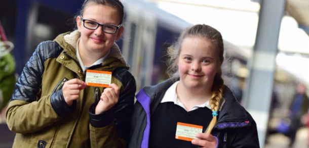Two girls holding train tickets in front of a train at the station platform.