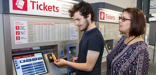 Woman helping young male use ticket machine